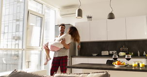 Homem latino-americano de sorriso feliz Carry Asian Woman, par romântico novo que gira Aroud junto na cozinha filme