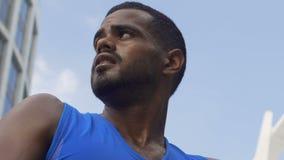 Homem latino-americano do atleta suado após o treinamento da sprint, resto após exercícios, ruptura filme