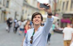 Homem latino-americano do moderno elegante novo com os óculos de sol que tomam um selfie Imagem de Stock