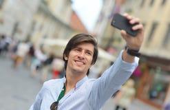 Homem latino-americano do moderno elegante novo com os óculos de sol que tomam um selfie Imagens de Stock