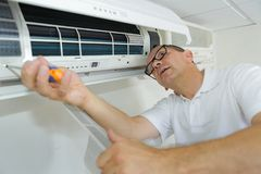 Homem latino-americano do reparo do condicionamento de ar que executa a manutenção fotos de stock royalty free