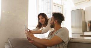 Homem latino-americano feliz Sit On Coach Asian Woman dos pares novos da raça misturada que usa o tablet pc junto