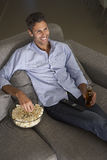 Homem latino-americano na tevê de Sofa Watching Foto de Stock Royalty Free