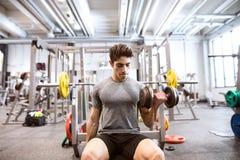 Homem latino-americano no gym que senta-se no banco, dando certo com pesos Fotografia de Stock