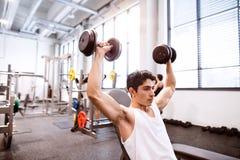 Homem latino-americano no gym que senta-se no banco, dando certo com pesos Imagens de Stock