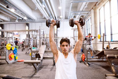 Homem latino-americano no gym que senta-se no banco, dando certo com pesos Imagem de Stock