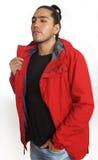 Homem latino-americano novo com a curva feita cabelo recolhida que veste o t-shirt preto e o revestimento vermelho, com uma mão e imagens de stock