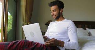 Homem latino-americano novo que usa a janela de sorriso feliz de Guy Chatting Online Over Big do laptop com opinião tropical do j vídeos de arquivo