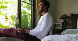 Homem latino-americano novo que usa a janela de sorriso feliz de Guy Chatting Online Over Big do laptop com opinião tropical do j filme