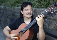 Homem latino-americano que joga a guitarra acústica fora Imagem de Stock Royalty Free