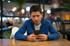 Homem latino-americano que relaxa usando o telefone no restaurante imagens de stock royalty free