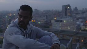 Homem latino-americano que toma o olhar ofendido ao redor, sentando-se no telhado, rejeção na sociedade filme