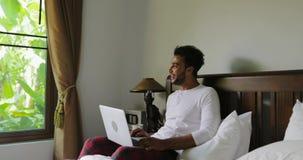 Homem latino-americano que usa o laptop que senta-se no quarto de Guy Type Chatting Online In da cama que olha na janela na vista filme