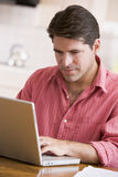Homem latino-americano que usa o portátil em casa Foto de Stock