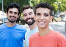 Homem latino com os dois amigos na cidade Fotografia de Stock Royalty Free