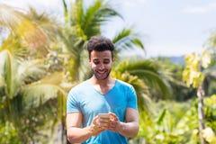 Homem latino feliz que usa o telefone esperto da pilha em linha sobre Forest Background tropical, retrato de Guy Chatting novo imagens de stock royalty free
