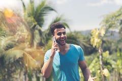 Homem latino que faz o telefonema sobre o indivíduo de sorriso feliz tropical da raça da mistura de Forest And Blue Sky Backgroun Imagem de Stock