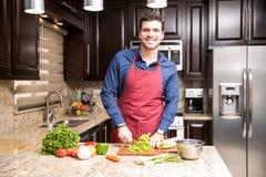 Homem latino que faz a salada do legume fresco Fotografia de Stock