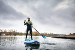 Homem levantar-se no paddleboard fotografia de stock royalty free