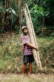 homem local do fazendeiro do aldeão com sua colheita grande da batata do 'batata doce' na borda de seu jardim tropical da selva foto de stock royalty free