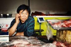 homem local no mercado que vende a carne desbastada quando no telefone imagens de stock