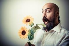 Homem longo da barba e do bigode que dá flores foto de stock