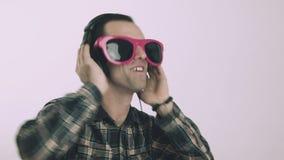 Homem louco com vidros grandes engraçados que escuta a música em fones de ouvido filme