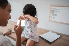 Homem louco em sua filha ao trabalhar no escritório domiciliário foto de stock