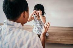 Homem louco em sua filha ao trabalhar no escritório domiciliário imagem de stock
