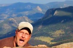 Homem louco que pendura no lado de uma montanha Fotografia de Stock Royalty Free