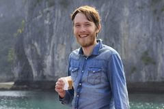 Homem louro atrativo branco novo com uma barba em uma camisa azul da sarja de Nimes que ri defiantly com um vidro do café no fund fotos de stock royalty free