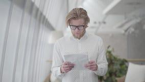Homem louro bem sucedido do retrato nos vidros que estão em papéis confortáveis claros de uma leitura do escritório Homem de neg? video estoque