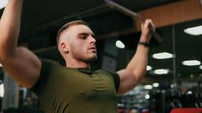 Homem louro considerável novo que iexercising seus músculos da caixa e que treina seus ombros no gym Disparado em 4k vídeos de arquivo