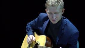 Homem louro que joga a guitarra acústica na fase no projetor, desempenho desconectado filme