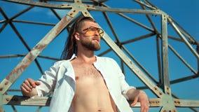 Homem macho da forma que tem os óculos de sol vestindo do penteado na moda que levantam no fundo da grade video estoque