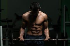 Homem macho que levanta peso com Barbell Fotos de Stock