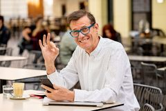 Homem maduro à moda atrativo de sorriso que usa o telefone esperto que trabalha o assento em linha fora da cafetaria fotografia de stock royalty free