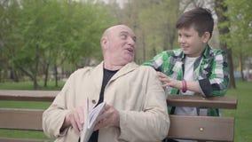 Homem maduro calvo ador?vel do retrato que senta-se no parque no banco que l? um livro Rapaz pequeno bonito que vem de atr?s vídeos de arquivo