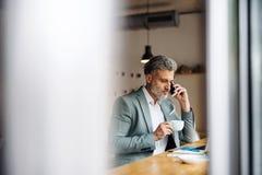 Homem maduro com café e smartphone na tabela em um café imagens de stock royalty free