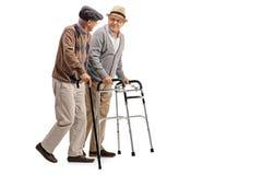 Homem maduro com caminhante e um outro homem com bastão foto de stock
