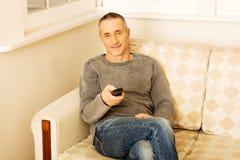 Homem maduro com controlo a distância imagem de stock royalty free