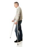 Homem maduro com muletas Imagem de Stock