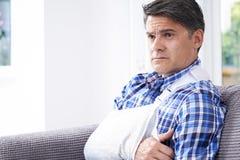 Homem maduro com o braço no estilingue em casa imagens de stock royalty free