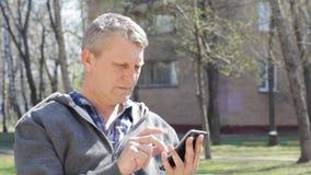 Homem maduro com o smartphone Fotografia de Stock