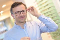 Homem maduro considerável do retrato que tenta vidros novos no ótico fotos de stock