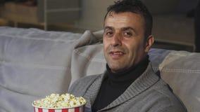 Homem maduro considerável que mostra os polegares acima ao sentar-se no cinema video estoque