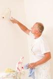 Homem maduro de decoração Home com rolo de pintura Fotografia de Stock Royalty Free