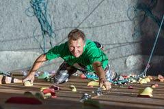 Homem maduro de sorriso na parede de escalada extrema imagens de stock royalty free
