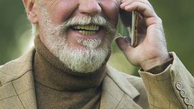 Homem maduro de sorriso que fala no smartphone, planos favoráveis da tarifa, conexão filme