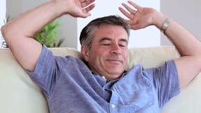Homem maduro de sorriso que relaxa em seu sofá filme